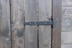Close up of old wooden door with rusty iron door hinge stock image