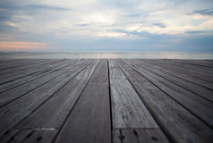 Close up old wooden flooring and tropical beach. Closeup of old wooden floors and a tropical beach at sunset Royalty Free Stock Photography
