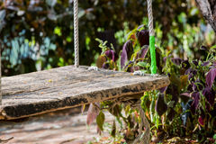 Close up old wooden vintage garden swing hanging from a large tr Royalty Free Stock Images