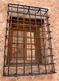 close up of an old wooden window with bars of iron blocking the access, in a wall of concrete and stone in an abandoned house stock image