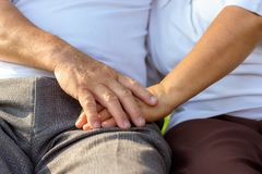 Close up older couple hands. Older husband use hand hold older wife's hand together for encouraging his beloved wife. stock photos