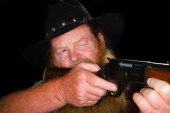 Close up of an older cowboy about to pull the trigger Stock Images