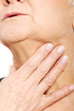 Close up on older woman's hand holding neck. Stock Photography