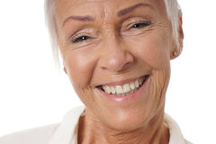 Close-up older woman with toothy smile. Close-up headshot of older woman in her sixties with toothy smile Royalty Free Stock Image