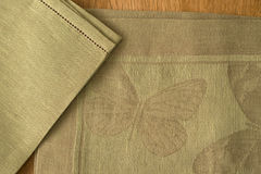 Close-up of Olive Green Placemat and Table Napkin Corners. Close-up of olive green placemat with embroidered butterfly design and an overlapping matching color Stock Photography