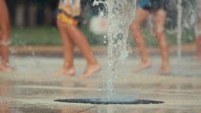 Close-up omhoog van kind` s voeten die en fontein in openbaar park spelen doornemen Ondiepe diepte van het gebied, gestemde video stock footage