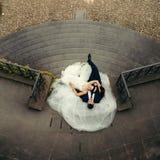 Close-up onderaan mening van het mooie jonggehuwdepaar die op de kleding van de bruid op de treden leggen De plaats van Praag stock foto's