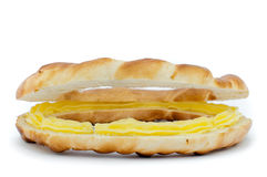 close-up of one bagel cut in two, with a yellow cream spread inside it Stock Photo