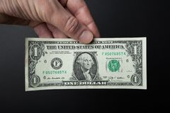 Close-up, one dollar in hand on a black background royalty free stock image
