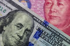 Close up of one hundred Dollar banknote over a 100 Yuan banknote with focus on portraits of Benjamin Franklin and Mao Tse-tung/USA. Vs China trade war concept royalty free stock photography