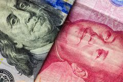 Close up of one hundred Dollar and 100 Yaun banknotes with focus on portraits of Benjamin Franklin and Mao Tse-tung/USA vs China t. Rade war concept stock image