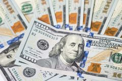 Close up of one hundred US dollar money bills spread on white ba Royalty Free Stock Images