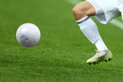 Close up one leg and feet of football player with the ball Royalty Free Stock Photo