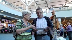 Close up of one old couple reading information retrieval at international arrival lobby stock video