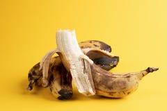 Close-up one peeled banana and two unpeeled overripe blackened ugly bananas on yellow background. Close-up one peeled banana and two unpeeled overripe blackened royalty free stock image