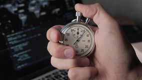 Close-up of one person starting up a stopwatch at hacker programmer screen background. Deadline concept. 4K, 10 BIT, 4:2