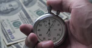 Close-up of one person starting up a stopwatch on money dollars background. Time is money. Deadline concept.