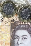 Close up of a One Pound Coin with a Ten Pound Note background - British Currency Stock Image