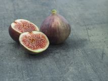 Close up one and two half of fresh ripen fig on grey textured ba Royalty Free Stock Photography