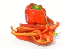 Close-up of one whole red bell pepper and one cut in pieces on white background. stock photography