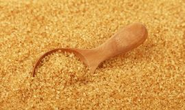 Close up wooden scoop spoon in brown cane sugar. Close up one wooden scoop spoon in brown cane sugar, high angle view, selective focus royalty free stock photos