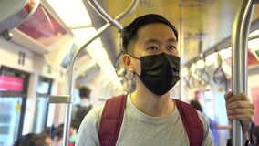 Close up of one young Asian man wearing a black surgical face mask in subway train during new type Coronavirus Covid-19
