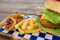 Close up of onion rings and french fries with burger. On cutting board Stock Photography