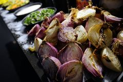 Close up onions cut in half and baked on a grill. Vegetarian food. Vegetarian food. Onions halves baked on a grill lie on the black wooden table salted. On a stock photography