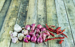 Close up onions,garlic and dry pepper on a wooden table Stock Photos