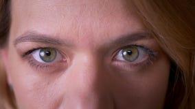 Close-up oog-portret van blondeleraar letten het op middelbare leeftijd calmly op in camera stock videobeelden