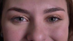 Close-up oog-portret van het mooie blondevrouw letten smilingly op in camera en het knipperen op zwarte achtergrond stock video