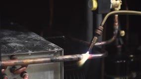 Close-up op buis van het soldeerlamp de smeltende koper samen met soldeersel klem Close-up van een mens wordt geschoten die een p stock videobeelden