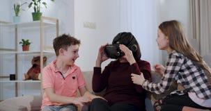Close-up op de bank een oma met haar kleinkinderen die tijd doorbrengen samen, jonge geitjes die voor het eerst een VR geven aan stock videobeelden