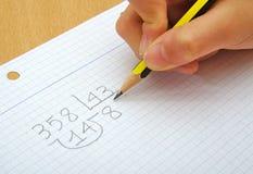 Close-up op de handen van een kind die wiskunde doen Stock Foto's