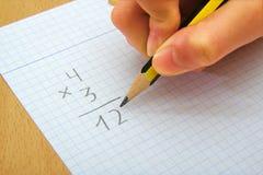 Close-up op de handen van een kind die wiskunde doen stock afbeelding