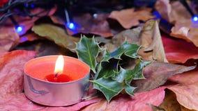 Close-up op een rode kaars en Kerstmishulst stock videobeelden