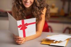 Close-up op gelukkige jonge Kerstmisprentbriefkaar van de huisvrouwenlezing Stock Foto's
