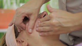 Close-up op gezicht van de therapeut die van de vrouwenmassage massage doen stock videobeelden