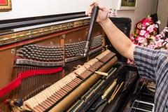 Close-up op hand die een pianino stemmen die hefboom en hulpmiddelen met behulp van stock foto's
