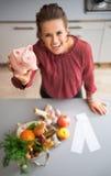 Close-up op huisvrouw die spaarvarken tonen Stock Afbeeldingen