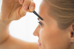 Close-up op jonge vrouw die wenkbrauwen uittrekken Stock Foto's