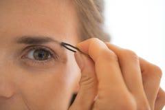 Close-up op jonge vrouw die wenkbrauwen uittrekken Stock Fotografie
