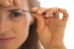 Close-up op jonge vrouw die wenkbrauwen uittrekken Royalty-vrije Stock Fotografie