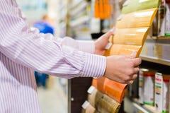 Close-up op mannelijke of vrouwelijke handen die verf voor hout in DIY-afdelingswinkel kiezen Stock Fotografie