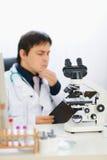 Close-up op microscoop en arts op achtergrond Stock Afbeeldingen