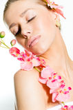 Close-up op mooie jonge dame met perfecte huid, gesloten ogen en van de de oorringsholding van luxejuwelen de orchideebloem Royalty-vrije Stock Foto