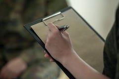Close-up op therapeut die nota's over stuk van document maken tijdens benoeming stock foto's