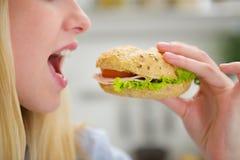 Close-up op tienermeisje die hamburger eten stock foto
