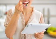Close-up op vrouw die salade eten en tabletpc met behulp van Stock Foto
