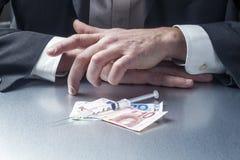 Close-up op zakenmanhanden met geld en spuit voor concept de gezondheidszorgindustrie royalty-vrije stock afbeeldingen